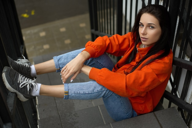 Молодая модная хипстерская женщина сидит на летней лестнице в красной куртке и синих джинсах