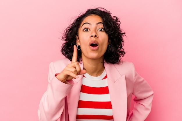 ピンクの背景にアイデア、インスピレーションのコンセプトを持つ若いトレンディなラテン女性。
