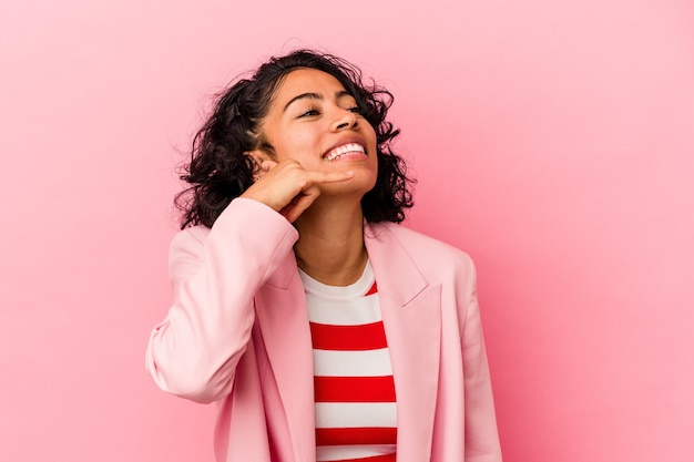 指で携帯電話の呼び出しジェスチャーを示すピンクの背景に分離された若いトレンディなラテン女性。