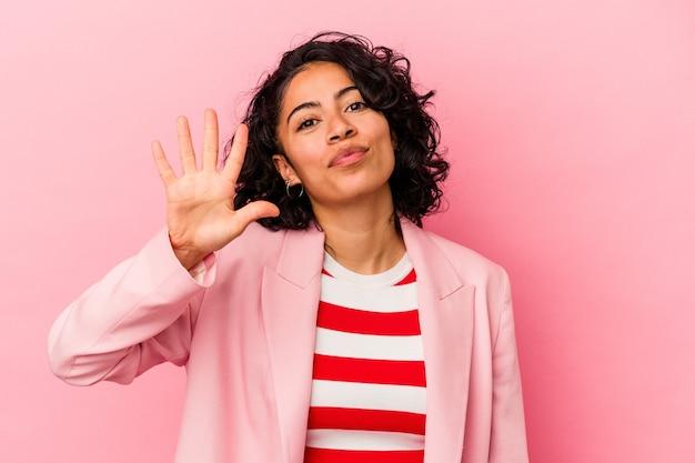 ピンクの背景に分離された若いトレンディなラテン女性は、指で5番を示す陽気な笑顔を浮かべています。