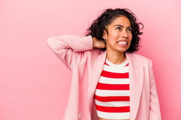 분홍색 배경에 고립된 젊은 트렌디한 라틴 여성은 머리 뒤쪽을 만지고 생각하고 선택합니다.