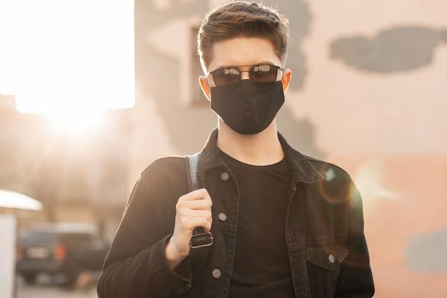 保護用の黒いマスクにサングラスをかけた若者のカジュアルな服を着たトレンディな若者