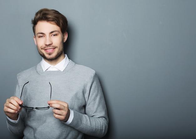 Молодой модный человек в очках, улыбаясь, студия выстрел