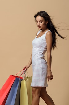 Young trendy woman carrying shopping bags on beige wall