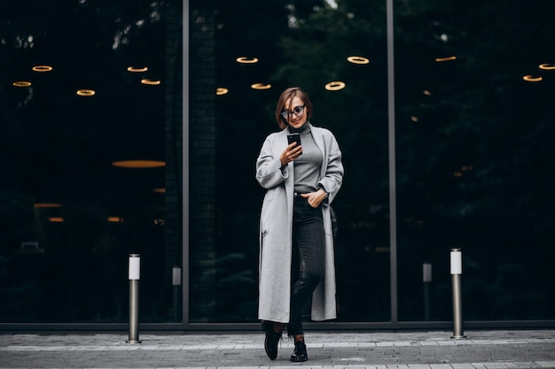 Young trendy woman in grey coat talking on the phone