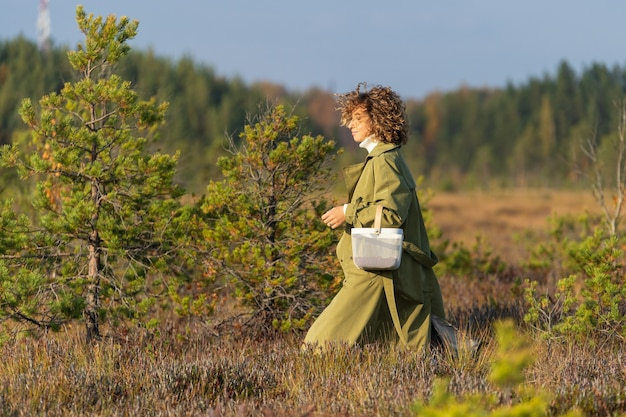 화창한 가을 날 크랜베리를 모으는 시골 산책을 하는 젊은 트렌디한 여성