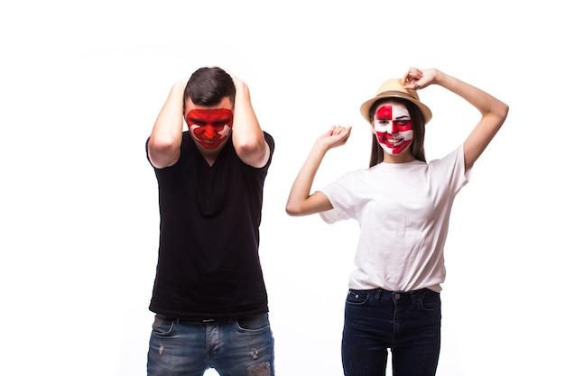 白い壁に分離された若いチュニジアとクロアチアのサッカーファン