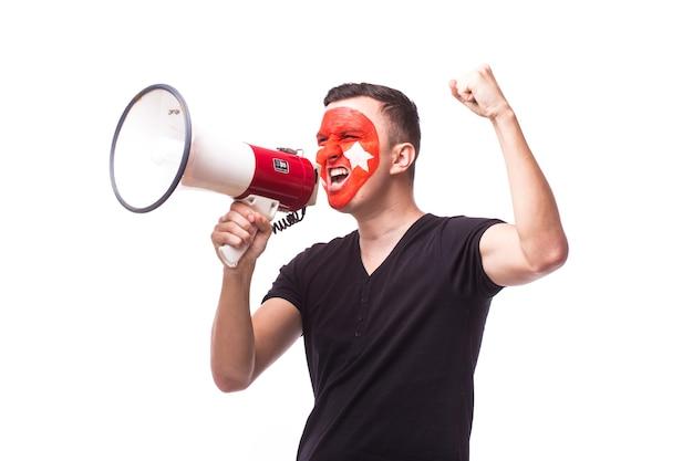 Молодой человек футбольного фаната туниса с мегафоном, изолированным на белой стене