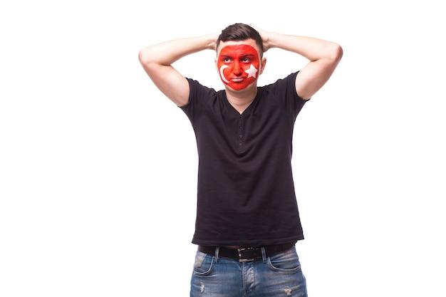 Молодой человек футбольного фаната туниса с грустным жестом изолирован на белой стене