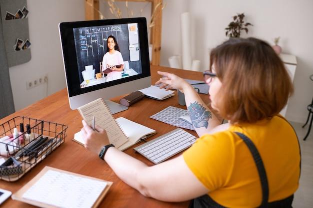 메모장을 들고 집에서 온라인 수업을 듣는 동안 학생 소녀를 묻는 젊은 교사