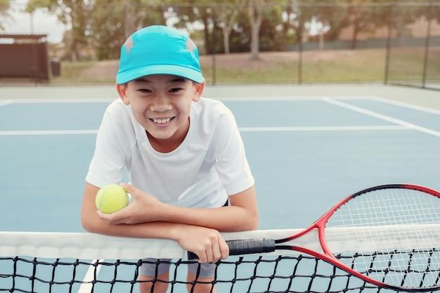 屋外の青いコートに若いトゥイーンアジアの男の子テニスプレーヤー