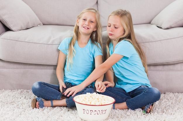Молодые близнецы едят попкорн, сидя на ковре