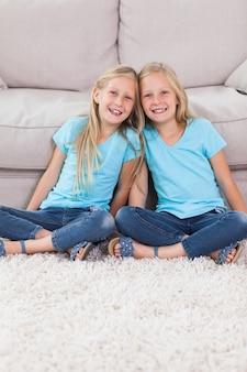 Молодые близнецы, сидящие на ковре