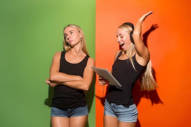 ラップトップを保持している若い双子の女性。