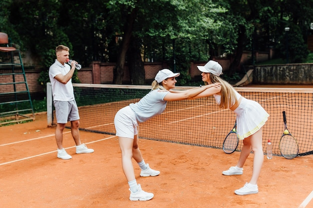Young two  female tennis player bending and touching her feet with both hands as a part of warm up workout on tennis court.