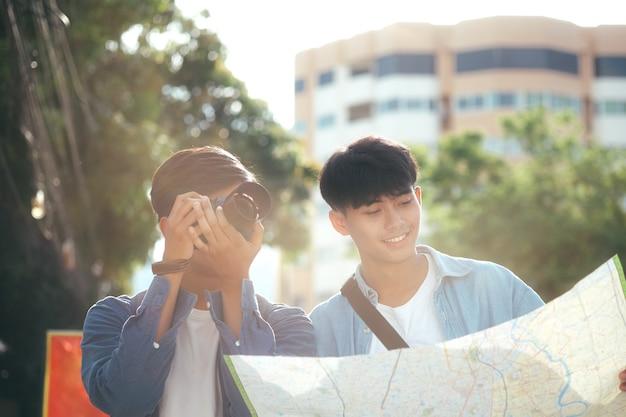 Молодые двое мужчин путешествовать вместе в городе на летние каникулы.
