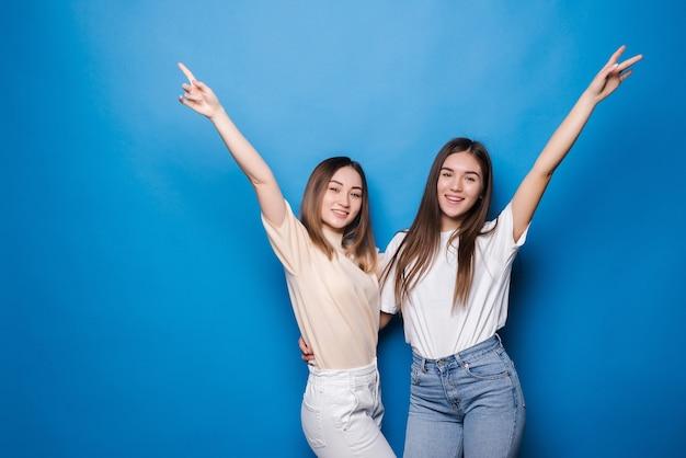 若い2人の女性が青い壁に孤立して祝う