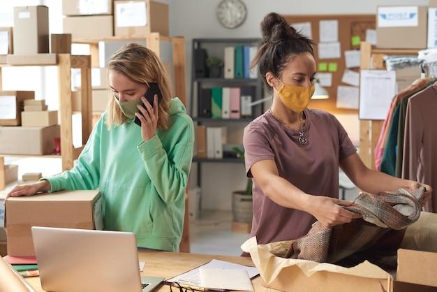 Две молодые женщины в защитных масках упаковывают одежду в коробки, работающие в службе доставки