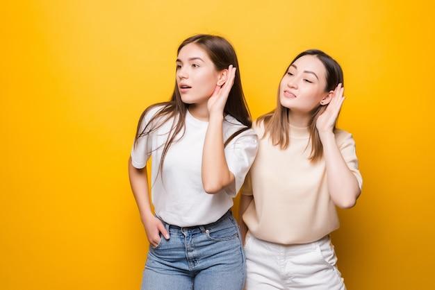 黄色の壁に隔離された耳に手を置くことによって何かを聞いている若い2人の女性