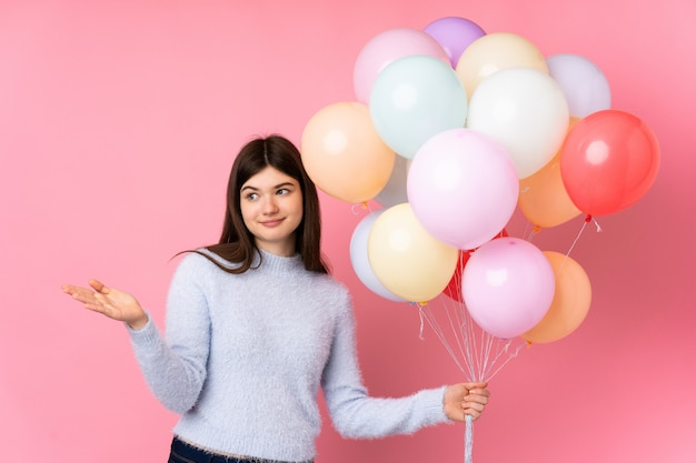 Young ukrainian teenager woman holding lots of balloons over isolated pink wall extending hands to the side for inviting to come