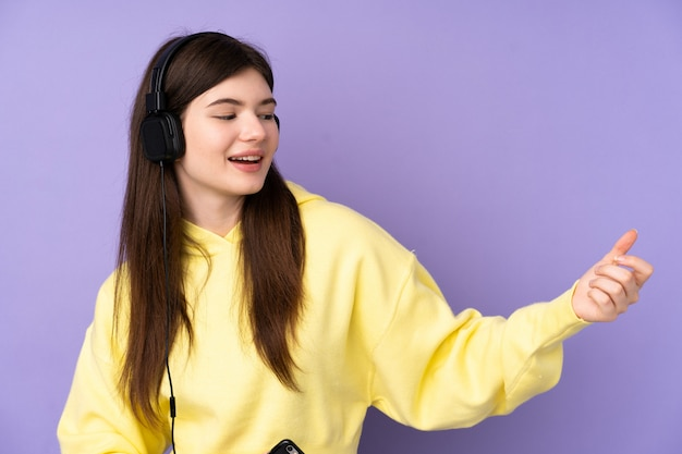 Young ukrainian teenager woman over isolated purple wall listening music and doing guitar gesture