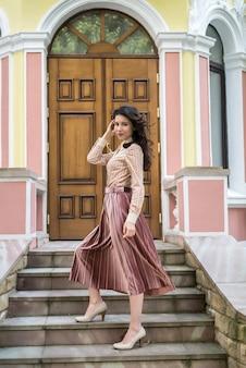 도시 거리의 현대적인 색상 건물 근처에 세련된 천을 입은 젊은 우크라이나 여성