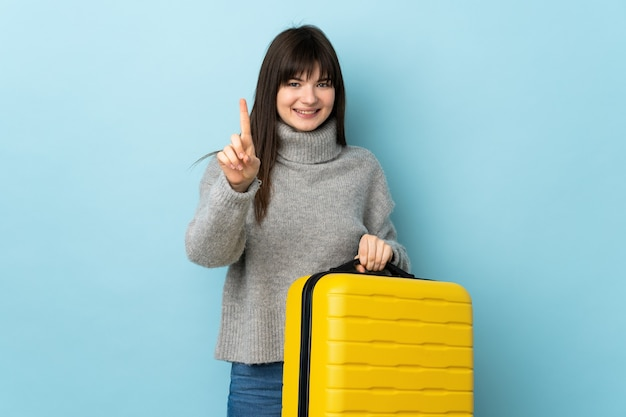 Young ukrainian woman isolated on blue wall in vacation with travel suitcase and counting one