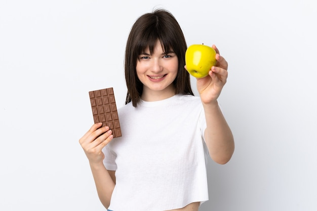 Молодая украинка изолирована на белой стене с шоколадной таблеткой в одной руке и яблоком в другой