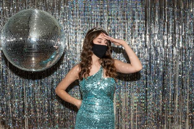 パーティーで黒い医療マスクの王冠とスパンコールの光沢のあるドレスを着ている若い不確かなかわいい女の子
