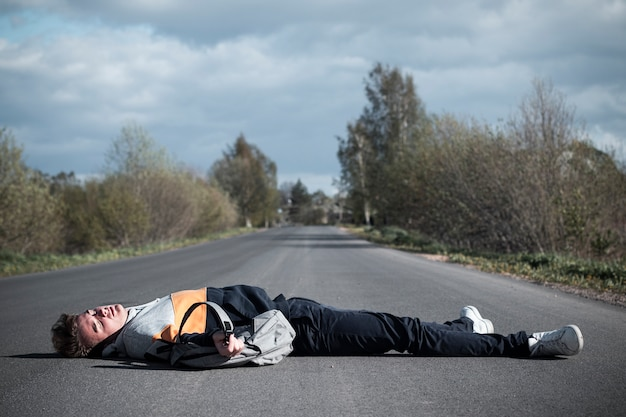 Young unconscious dead man at accident scene, crash on the road. pedestrian guy, teenager hit by a car on the road while crossing highway. downed male person is lying on asphalt. dangerous situation