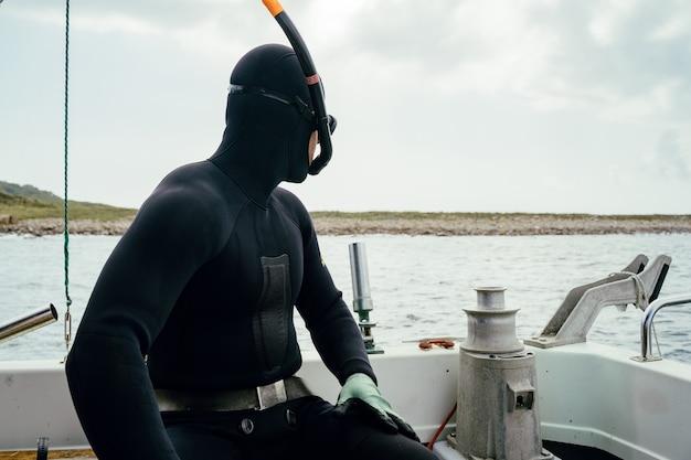 ボートでダイビングする準備をしている若い水中ハンターダイバー