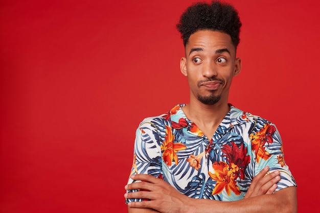 Young unhappy african american guy wears in hawaiian shirt, looking left at the copy space, stands over red background with crossed arms.