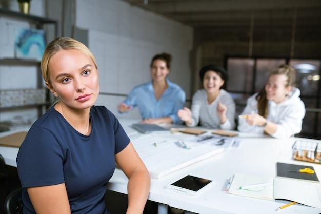 彼女にうめき声を上げる3人の笑っている女の子の背景に机のそばに座っている青いtシャツの若い不幸なブロンドの女性