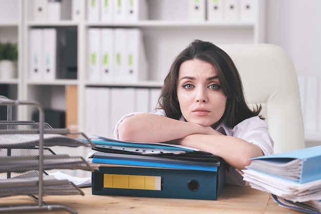 Young unhappy female accountant or secretary lying on thick stack of financial papers while sitting by desk in front of camera