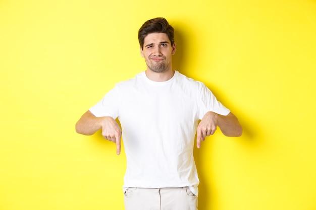 顔をゆがめ、広告に指を下に向け、製品に失望し、黄色の背景の上に立っている若い不幸な男。