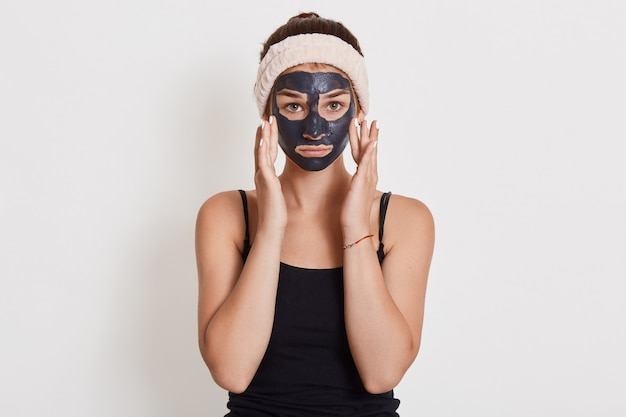 白い壁に分離されて立っている顔に黒い化粧品のマスクを持つ若い不幸な主婦、指で彼女の頬に触れる