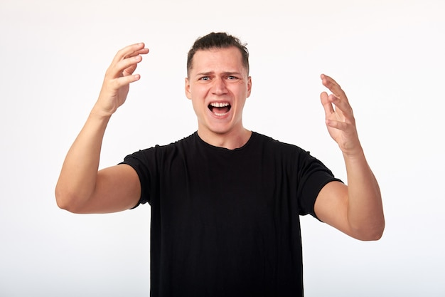 Young unhappy man screaming, quarreling while standing against white