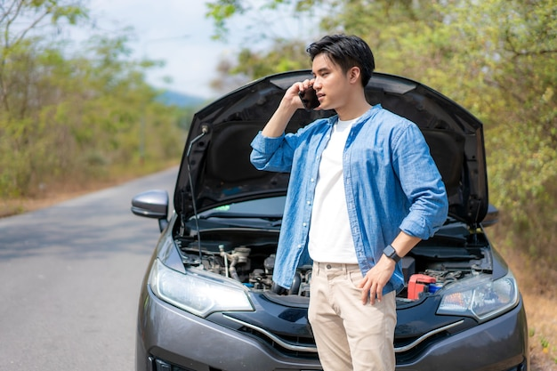 Young unhappy man talking on a cell phone in front of the open hood  broken down car