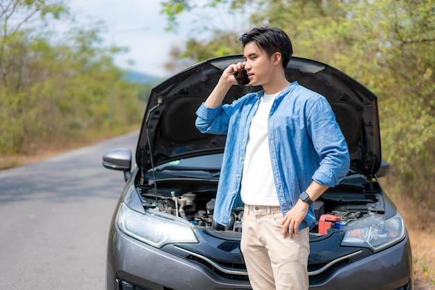 車を分解オープンボンネットの前で携帯電話で話している若い不幸な男