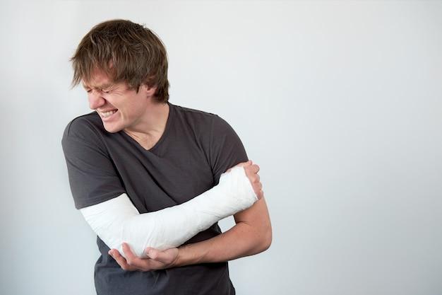 고통으로 고통받는 그의 팔에 석고 캐스팅으로 젊은 불행한 남자