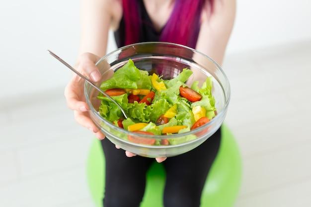 野菜サラダと巻尺を持っている若い正体不明のフィットネスブロガーの女の子。スポーツライフスタイルと適切な栄養の概念