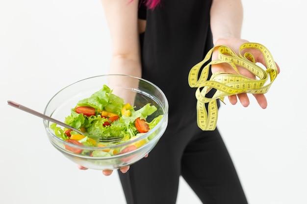 野菜サラダを保持し、スポーツの巻尺の概念を保持している若い正体不明のフィットネスブロガーの女の子