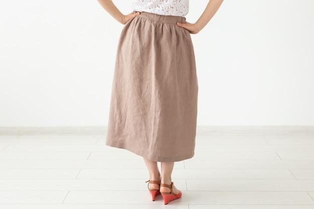 茶色の長いスカートと靴を履いた正体不明の少女が白い壁の近くに立っています。フェミニンなデザイン商品のコンセプト。広告スペース