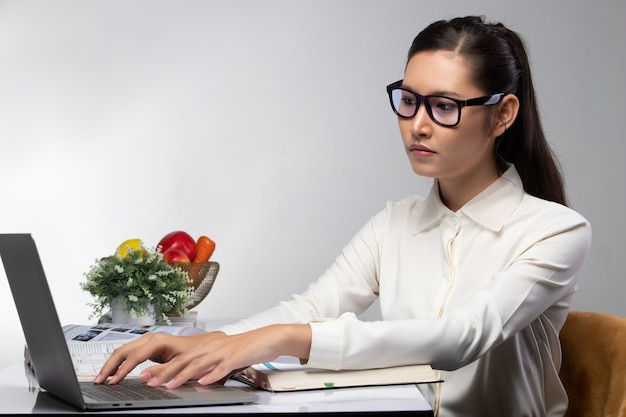 Young university asian woman student wearing purple glasses research and searching information on computer laptop notebook