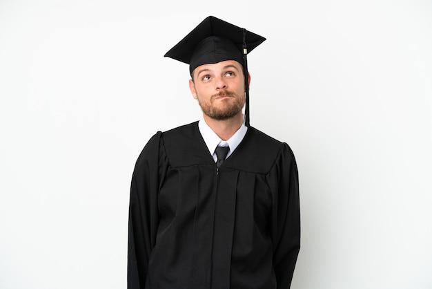 若い大学ブラジルの卒業生は白い背景で隔離され、見上げる