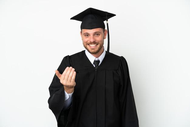 젊은 대학 브라질 졸업생은 흰색 배경에 격리되어 손을 잡고 초대합니다. 당신이 와서 행복