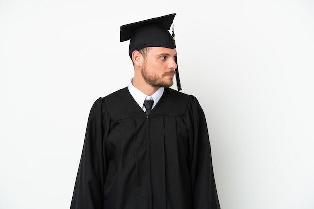 Молодой бразильский выпускник университета изолирован на белом фоне, глядя в сторону