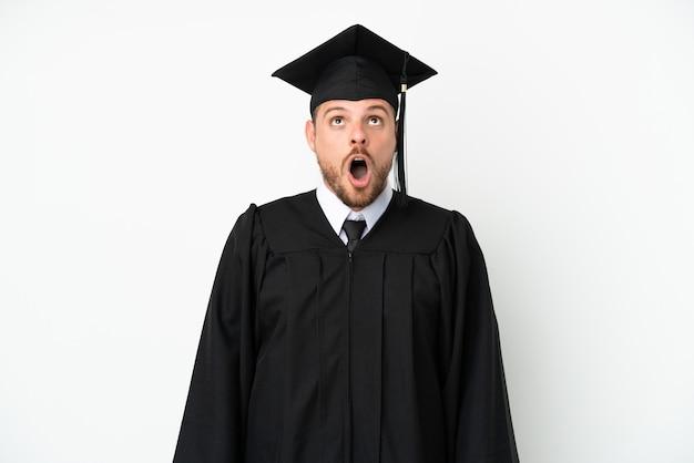 見上げると驚いた表情で白い背景に分離された若い大学ブラジルの卒業生