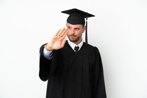 Молодой бразильский выпускник университета изолирован на белом фоне, делая жест стоп и разочарованный