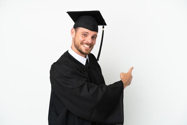 다시 가리키는 흰색 배경에 고립 된 젊은 대학 브라질 대학원